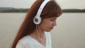 Flickan i hörlurar promenerar stranden med minnestavlan och lyssnar till musik, flickakontrollpost på en minnestavla direktanslut fotografering för bildbyråer