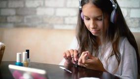 Flickan i hörlurar som direktanslutet pratar på bitande telefondanandemanikyr, spikar med fri och kopieringsutrymme lager videofilmer