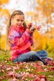Flickan i höst parkerar royaltyfri foto