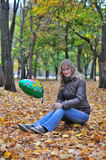 Flickan i höst parkerar med ballongen sitter på stubben royaltyfri foto