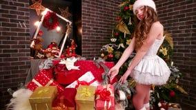 Flickan i hatt för jultomten` s förbereder ferieaskar för jul, nära julgranfamiljgåvor, systern förbereder sig för arkivfilmer