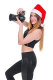 Flickan i hatten av Santa Claus med en kamera Ung flickafotograf Christmas Julselfie Arkivfoto