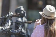 Flickan i hatten fotograferas på telefonen per stycke av konst arkivbilder