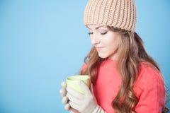 Flickan i hatten fryste och dricka varmt te Arkivfoton