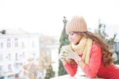 Flickan i hatten fryste och dricka varmt te Royaltyfri Bild