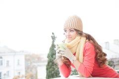 Flickan i hatten fryste och dricka varmt te Arkivbild