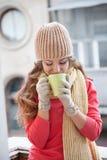 Flickan i hatten fryste och dricka varmt te Arkivbilder