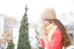 Flickan i hatten fryste och dricka varmt te Arkivfoto