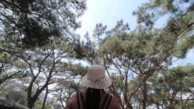 Flickan i hatten går långsamt till och med parkerar fullt av träd lager videofilmer