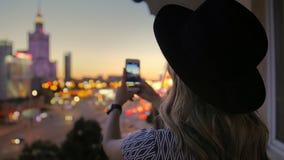 Flickan i hatten gör ett foto av nattstaden Använder en smartphone I ramen av en skyskrapa i mitten av arkivfilmer