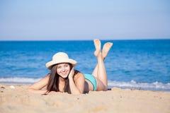 Flickan i hatten solbadar på stranden Arkivbild