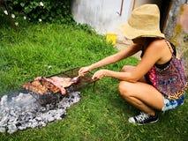Flickan i hatten som grillar argentinskt nötkött på trädgårdgallret på gräset arkivfoton