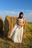 Flickan i hayloften med bröd och en handduk Arkivfoton