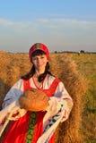 Flickan i hayloften med bröd och en handduk Arkivbild