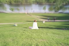Flickan i hennes kläder som ser som på en vit ängel, sitter tillbaka Arkivfoto