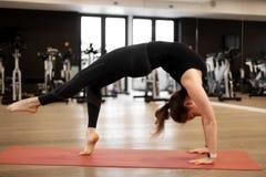 Flickan i idrottshallen g?r yoga f?r att h?lla sig i form eller kontroll?verskottvikt royaltyfria foton