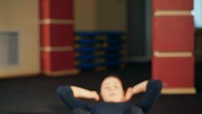 Flickan i idrottshallen utför en övning på de buk- musklerna Blöda press stock video