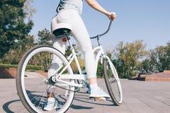 Flickan i jeans och t-skjorta sammanträde på en tappningblått cyklar i p arkivfoton
