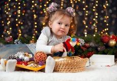 Flickan i julgarnering med gåvan, mörk bakgrund med belysning och boke tänder, begreppet för vinterferie Arkivbild
