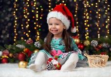 Flickan i julgarnering med gåvan, mörk bakgrund med belysning och boke tänder, begreppet för vinterferie Arkivbilder