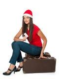 Flickan i jultomten en hjälpredahatt sitter på en resväska Fotografering för Bildbyråer