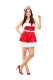 Flickan i jultomten kostymerar benägenhet mot en vägg Arkivfoto
