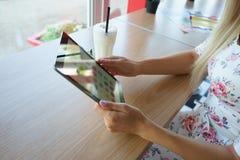 Flickan i kafé med minnestavlan i händer Royaltyfria Foton