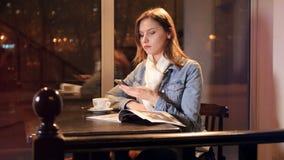 Flickan i kafét som ringer mobiltelefonen glidare Stående 4K arkivfilmer