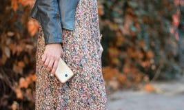 Flickan i klänningen rymmer telefonen royaltyfria foton
