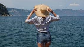 Flickan i kortslutningar för en blå skjorta och grov bomullstvillstår vid havet i en sugrörhatt stock video