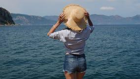 Flickan i kortslutningar för en blå skjorta och grov bomullstvillstår vid havet i en sugrörhatt lager videofilmer