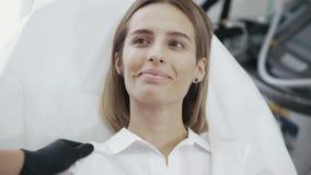 Flickan i kosmetologens kontorsleenden, rynkar pannan, blinkar och showansiktsuttryck för kosmetiska tillvägagångssätt, injektion lager videofilmer