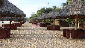 flickan i lång klänning poserar på stranden bland solparaplyer lager videofilmer