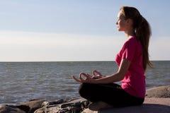 Flickan i lotusblomma poserar att sitta nära havet Arkivfoto