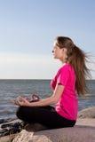 Flickan i lotusblomma poserar att sitta nära havet Arkivfoton
