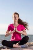 Flickan i lotusblomma poserar att sitta nära havet Arkivbild