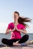 Flickan i lotusblomma poserar att sitta nära havet Arkivbilder