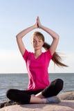 Flickan i lotusblomma poserar att sitta nära havet Royaltyfri Bild