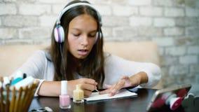 Flickan i lyssnande musik för hörlurar och för hemkläder på att applicera för telefondanandemanikyr spikar polermedel lager videofilmer