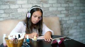 Flickan i lyssnande musik för hörlurar på att applicera för telefondanandemanikyr spikar utrymme för den fria kopian för polermed arkivfilmer