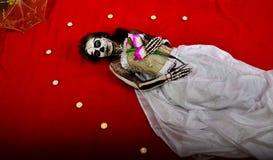 Flickan i makeupen av skelettet ligger bland stearinljusen Fotografering för Bildbyråer