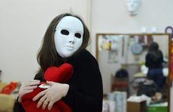 Flickan i maskeringen med en röd hjärta i händer Arkivfoto