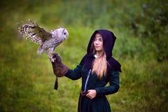 Flickan i medeltida klänning rymmer en uggla på hennes arm Royaltyfria Bilder