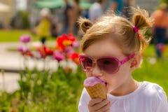 Flickan i modeexponeringsglas äter glass Barn och läcker glass Royaltyfri Bild
