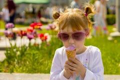 Flickan i modeexponeringsglas äter glass Barn och läcker glass Arkivbild