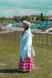 Flickan i nationell Bashkir kläder står på 'Sabantui 'ferie, sidosikt royaltyfri foto