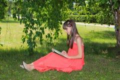 Flickan i natur i en röd klänning läser en bok Royaltyfri Fotografi