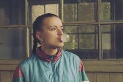 Flickan i ninetiesna blåser upp att tugga bubblan arkivbild