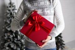 Flickan i nytt års tröja med hjortar rymmer i hand en röd ask med en gåva och en pappersexercis mot bakgrunden av ettträd royaltyfri foto