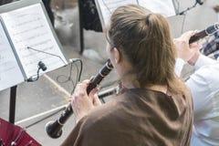 Flickan i orkestern spelar klarinetten arkivbild
